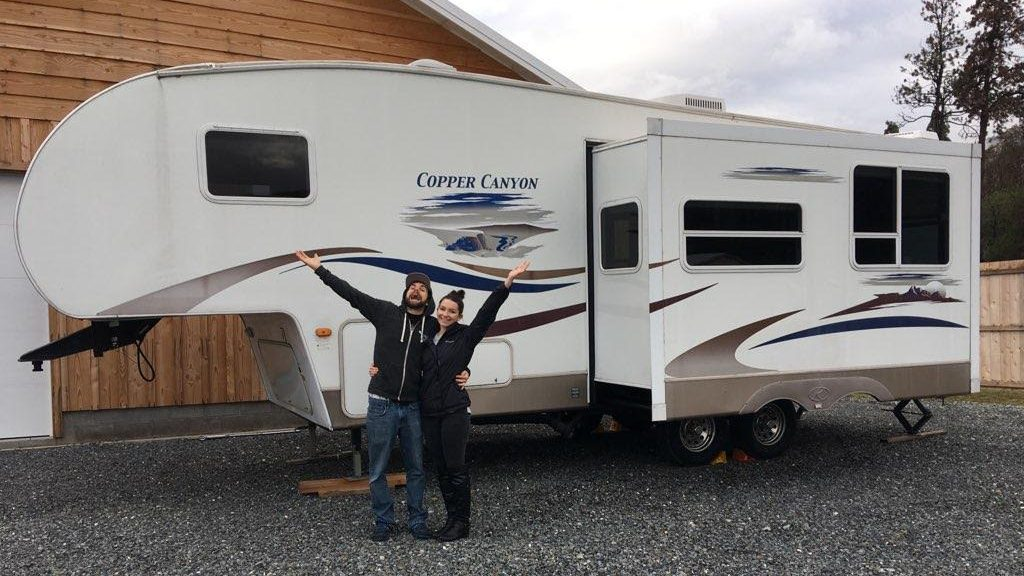 Jeremiah Svaren and Ashley Fitch celebrating in front of their new home, a renovated 5th wheel RV.